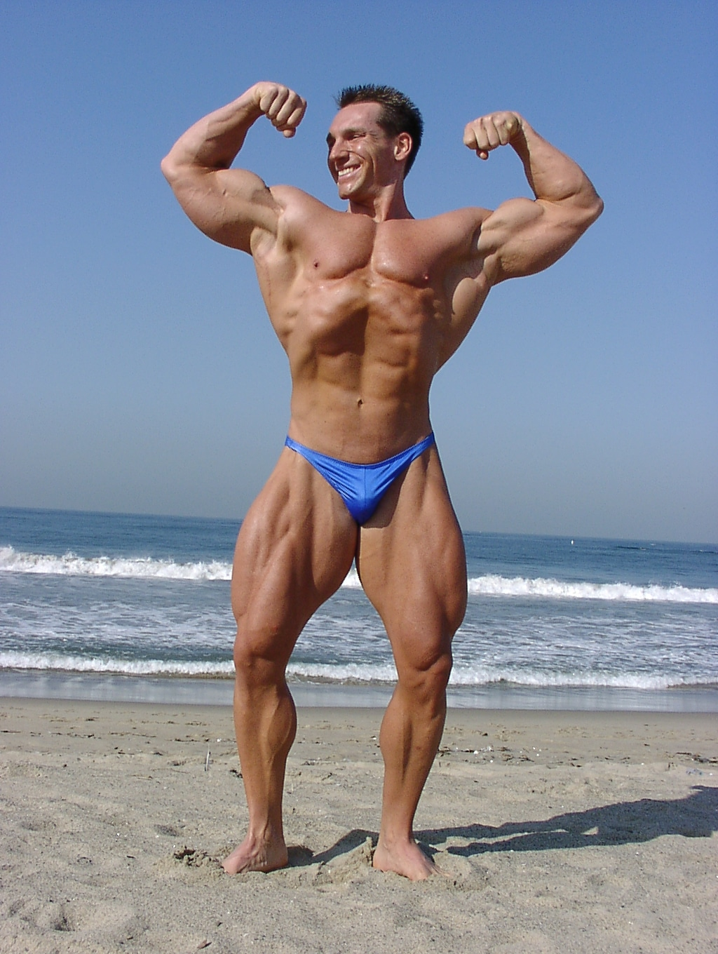 bodybuilder front double biceps pose on beach